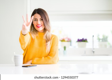 Young beautiful woman drinking a cup of coffee at home showing and pointing up with fingers number three while smiling confident and happy.
