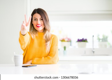 Young beautiful woman drinking a cup of coffee at home showing and pointing up with fingers number two while smiling confident and happy.