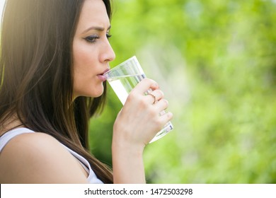 Young beautiful woman drinking glass of water over nature isolated background