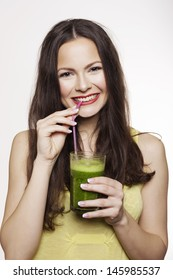Young beautiful woman drinking a healthy raw fruit vegetable juice. Studio shot