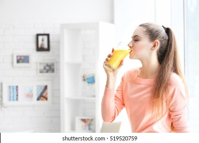 Young beautiful  woman drinking juice