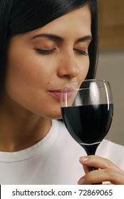 Young beautiful woman drinking red wine.