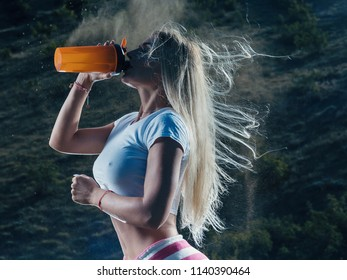 Young beautiful woman drinking sports nutrition during workout training. Sexy athletic girl drinking water outdoor.