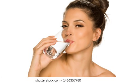 Young beautiful woman drinks water from the glass on white background