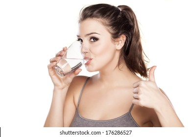 young beautiful woman drinks water from a glass and showing thumbs up