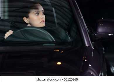 young beautiful woman driving a car and smiling