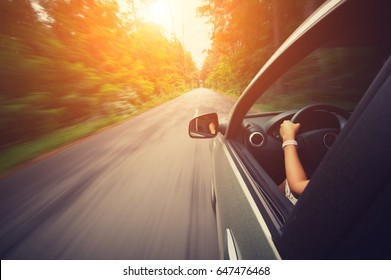 Young beautiful woman driving car at sunny day - outside view
