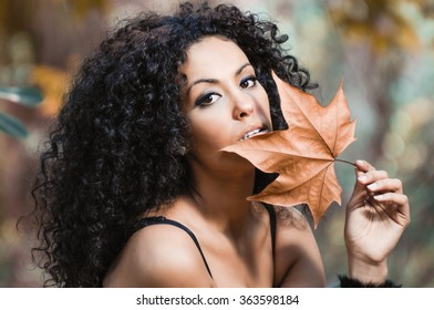Young beautiful woman with a dry leaf in an urban park
