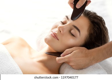 Young and beautiful woman during Chinese traditional massage - Gua Sha