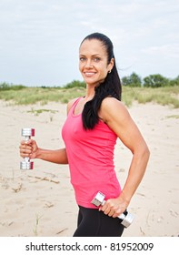 Young beautiful woman during fitness on sea beach