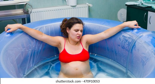 Young beautiful woman during labour right before giving birth in water.