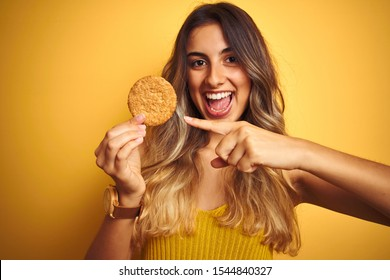Young beautiful woman eating biscuit over grey isolated background very happy pointing with hand and finger
