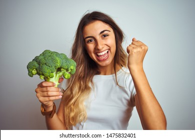 Young beautiful woman eating broccoli over grey isolated background screaming proud and celebrating victory and success very excited, cheering emotion