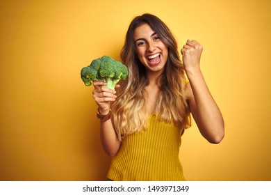 Young beautiful woman eating broccoli over yellow isolated background screaming proud and celebrating victory and success very excited, cheering emotion
