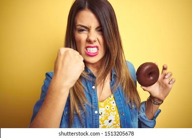 Young beautiful woman eating chocolate donut over yellow background annoyed and frustrated shouting with anger, crazy and yelling with raised hand, anger concept