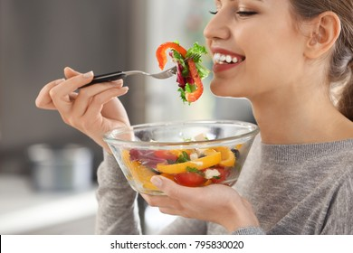 Young beautiful woman eating fresh salad on blurred background