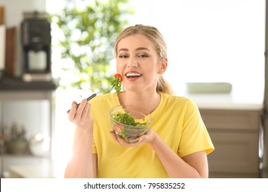 Young beautiful woman eating fresh salad in kitchen