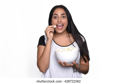 Young beautiful woman eating popcorn. Isolated white background