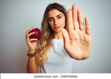 Young beautiful woman eating red apple over grey isolated background with open hand doing stop sign with serious and confident expression, defense gesture