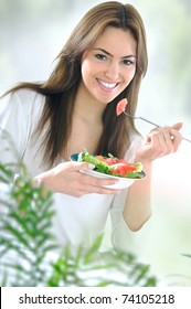 young beautiful woman eating salad
