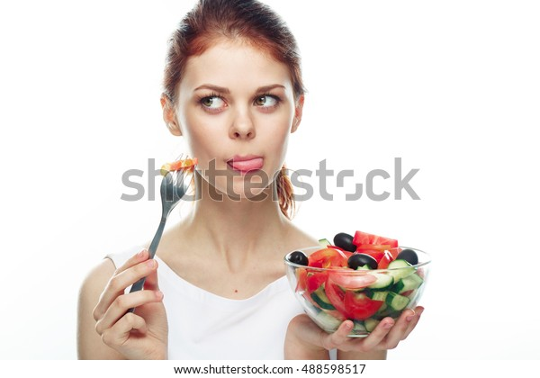 young beautiful woman eating a salad. Isolated background. Woman eating