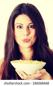Young beautiful woman eating spaghetti