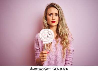 Young beautiful woman eating sweet candy over pink isolated background with a confident expression on smart face thinking serious