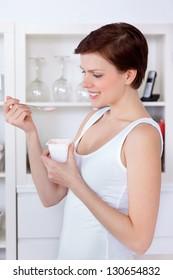 Young beautiful woman eating yogurt as breakfast or snack