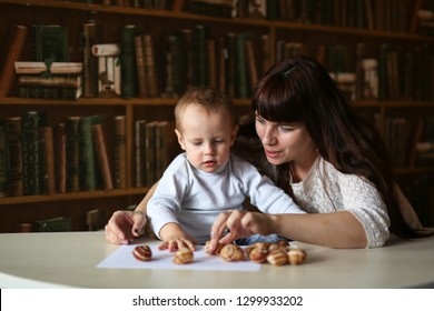 young beautiful woman educator deals with the child Toddler boy with the help of developmental benefits, the concept of earlier development and activities with children.