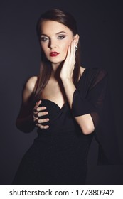 Young beautiful woman in elegant black dress dark studio background