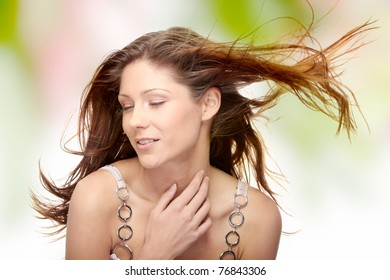 Young beautiful woman in elegant, evening, white dress dancing with wind (hair blowing).