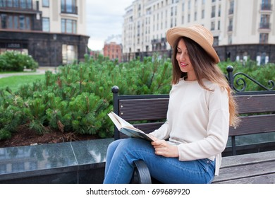 A young beautiful woman in an elegant hat sits on a bench in a new residential neighborhood and reads a paper book. She flips through the pages and smile. Urban background.