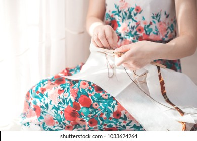 Young beautiful woman is engaged in embroidering a dagger on the embroidery frame in a colored dress at the window in the sunlight. A great picture for a hobby