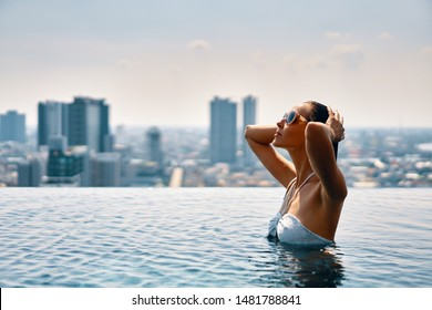 Young beautiful woman enjoy summer vacation on swimming pool in hotel roof top . Travel and relax concept