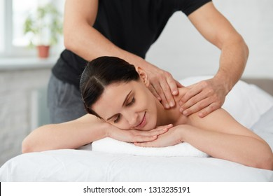 Young beautiful woman enjoying a back massage. Professional massage therapist is treating a female patient in apartment. Relaxation, beauty, body and face treatment concept. Home massage.