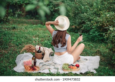 Young beautiful woman enjoying ealthy picnic for a summer vacation with freshly baked croissants, fresh fruit and fruit salad, sandwiches and a glass of red vine laid out on white cloth