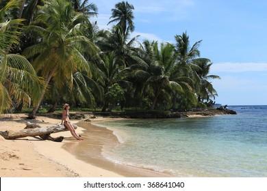 "Young beautiful woman enjoying her time and resting close to the sea in the southern beach of ""Pelicano"" Island, close to Yandup Island lodge, kuna indians territory, San Blas, Panama"