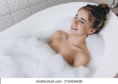 A young beautiful woman is enjoying a hot bath