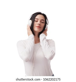 Young beautiful woman enjoying with listening the music in headphones against white background