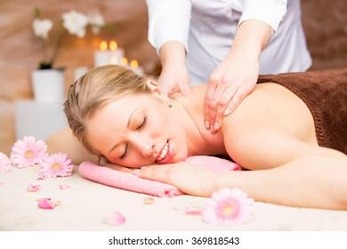 Young beautiful woman enjoying massage at spa studio