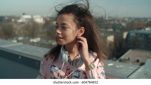 Young beautiful woman enjoying time on a rooftop. Fashion young African American woman relaxing in a city.