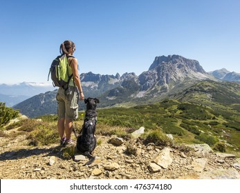 young beautiful woman enjoying the view with her dog during hiking trip in the mountain