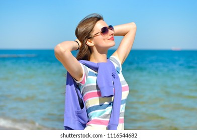 Young beautiful woman enjoys relaxing at the sea. She stands and tans on a blue sea background