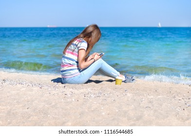 Young beautiful woman enjoys relaxing at the sea. She sits on the sand on a blue sea background with a smartphone in her hands
