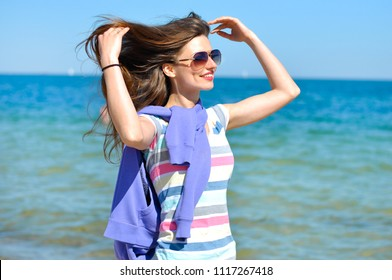 Young beautiful woman enjoys relaxing at the sea. She straightens her hair and the wind blows them