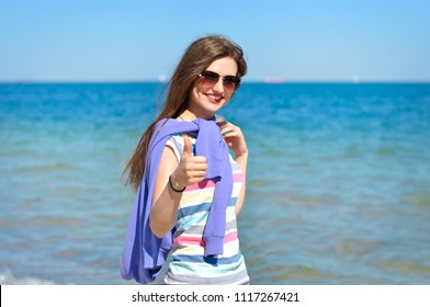 young beautiful woman enjoys relaxing at the seaside. She smiles and shows her thumbs up