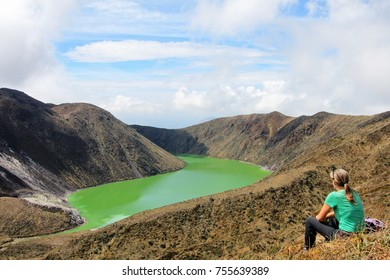 Young beautiful woman enjoys the view and the deep green colors of Laguna Verde lake in Narino, Colombia.