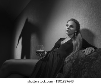 Young  beautiful woman in evening dress with glass of brandy and the culprit shadow on the wall. Black and white. Noir style.