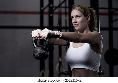 Young beautiful woman exercising with kettlebell