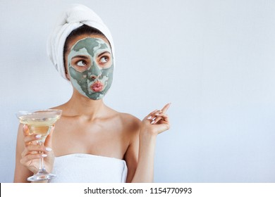 Young beautiful woman in face mask of therapeutic blue mud with champagne. Spa treatment, self care and healthy skin. Copy space, white background